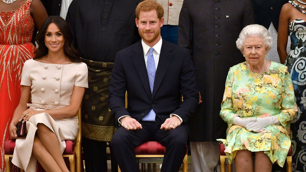 """Britain's Queen Elizabeth, Prince Harry and Meghan, the Duchess of Sussex sit in a line against a backdrop of some of Queen""""s Young Leaders at a Buckingham Palace reception following the final Queen""""s Young Leaders Awards Ceremony, in London, Britain June 26, 2018."""
