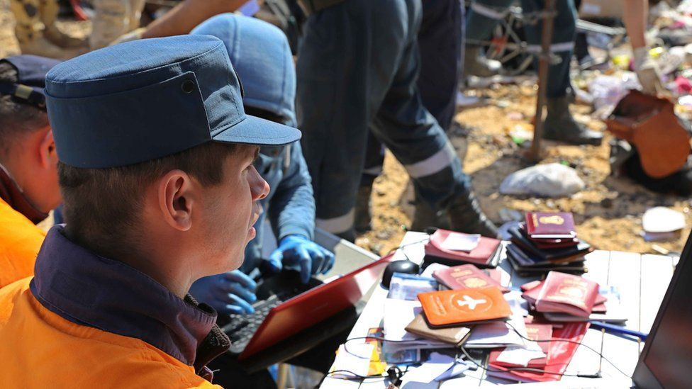 Russian rescuer checking passports collected from the wreckage of crashed plane in photo released by Russia's Emergency Ministry (2 November 2015)