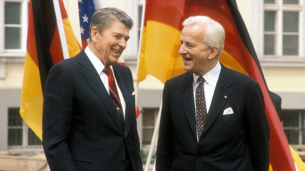 Ronald Reagan and Richard von Weizsaecker stand together in front of American and German flags