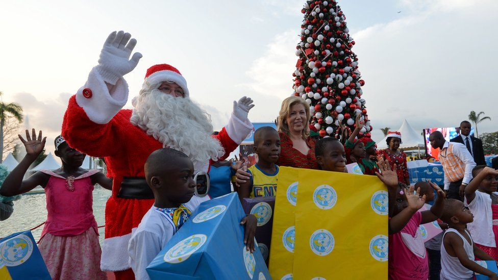 A man dressed as Santa poses with Ivory Coast's first lady Dominique Ouattara (C) and children at the presidential palace in Abidjan.