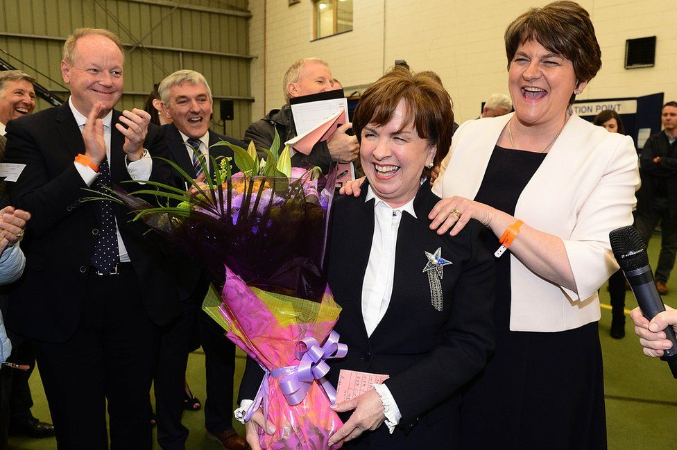 Diane Dodds holding a bouquet of flowers and being congratulated by Arlene Foster and other DUP colleagues