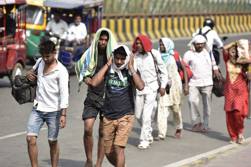 People cover themselves to beat the heat on a summer day, as temperatures in the capital reach 45 degree Celsius, on May 31, 2019 in Noida, India.