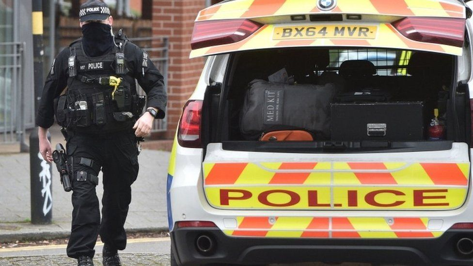 A firearms officer walks to his vehicle