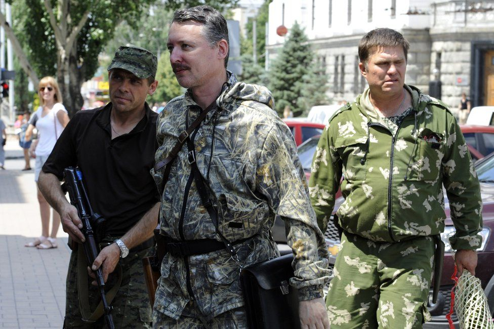 Igor Girkin, aka Strelok (C), walks with his bodyguards in the eastern Ukrainian city of Donetsk on 11 July 2014