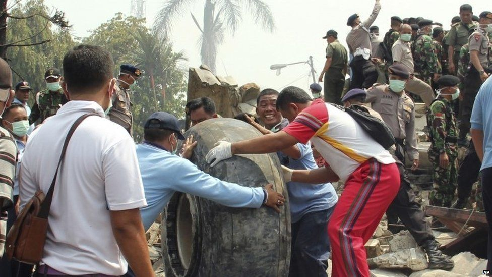 Military personnel remove an aircraft wheel at the site where an air force cargo plane crashed in Medan, Indonesia (30 June 2015)