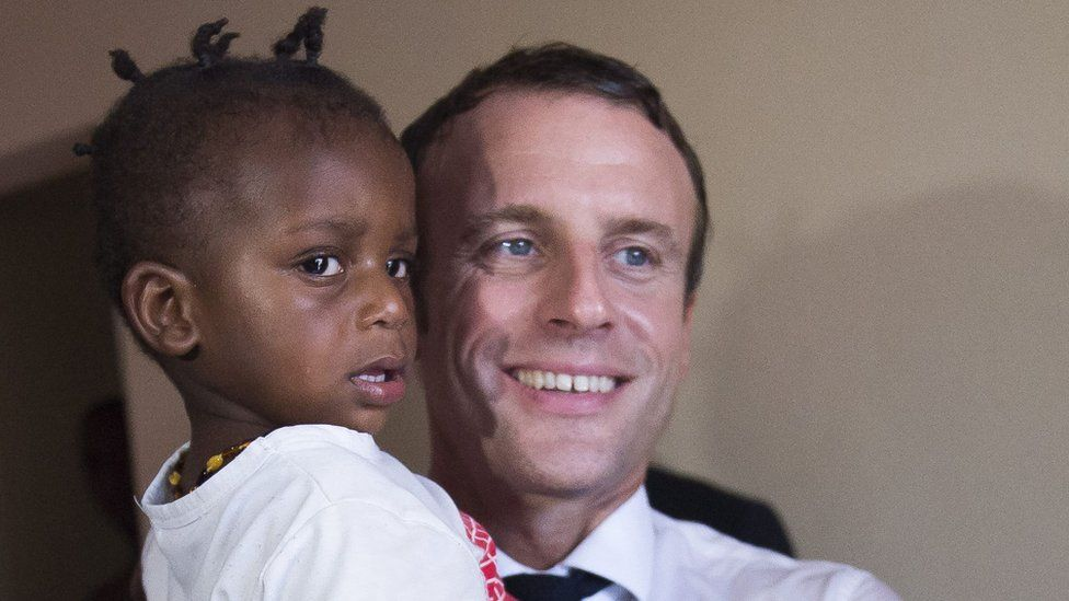 French President Emmanuel Macron holds a child as he meets residents of Quartier Orleans, 29 September 2018