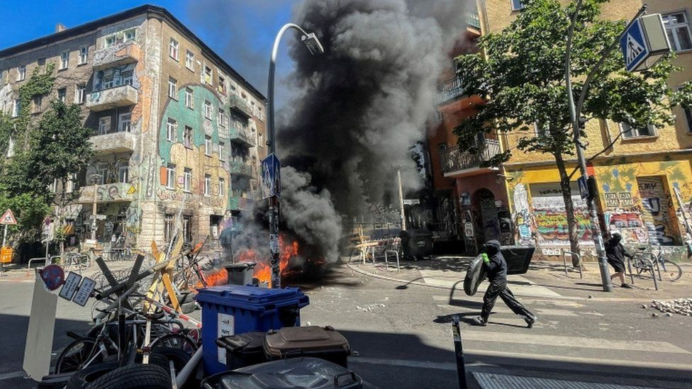 A man holding an object runs toward burning barricades at Rigaer Street in Berlin