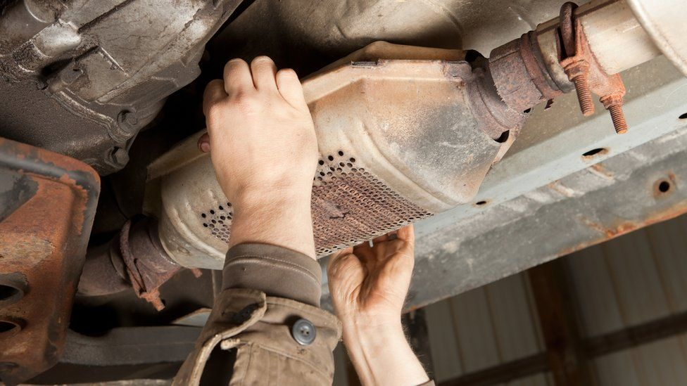 A catalytic converter being removed from an SUV car