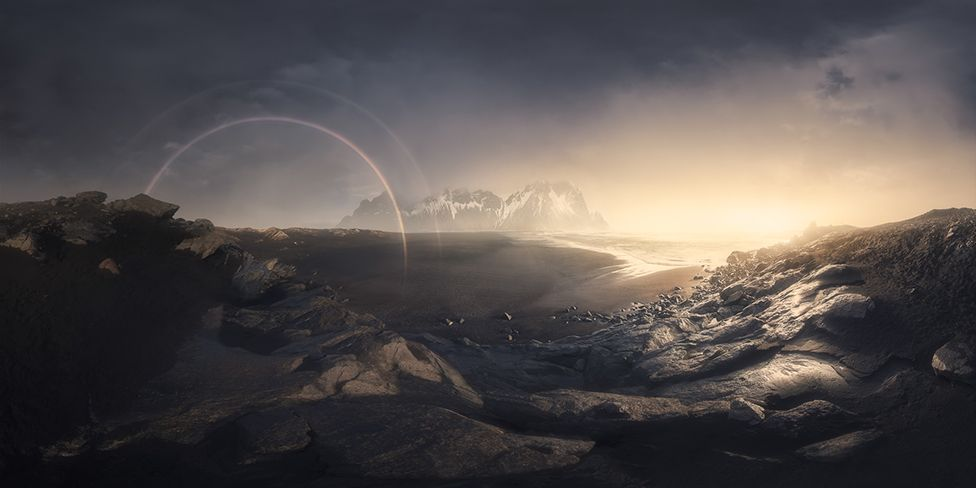 A mountain landscape view of a sunrise and a rainbow