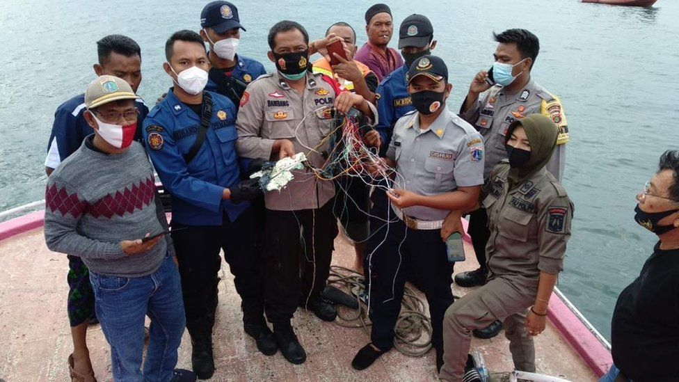 Police officers and fishermen show debris that they believe came from the plane