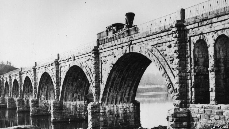 1859: A steam train on the Columbia Railway Bridge, crossing the Schuylkill River in Pennsylvania.
