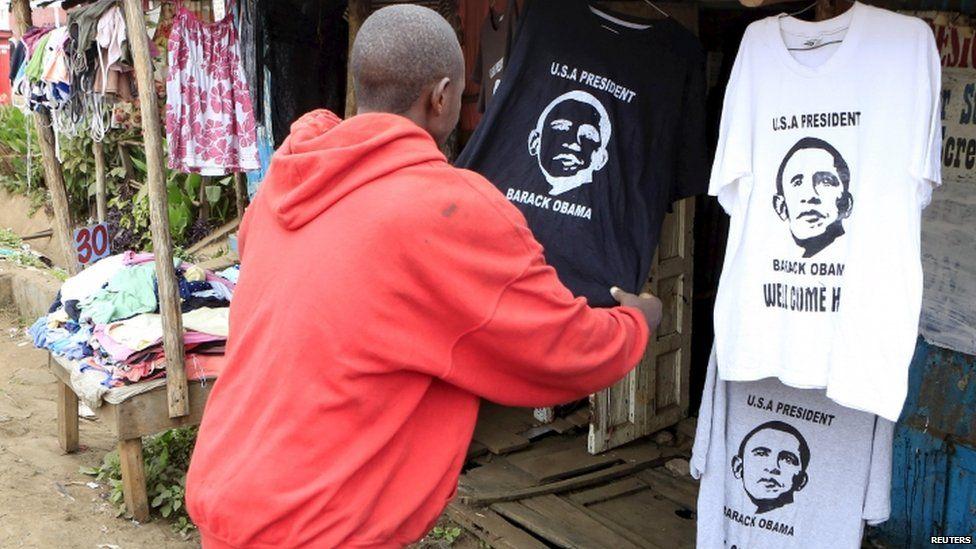 Customer looks at Obama shirts at a stall in Nairobi's Kibera slums, 23 July 2015