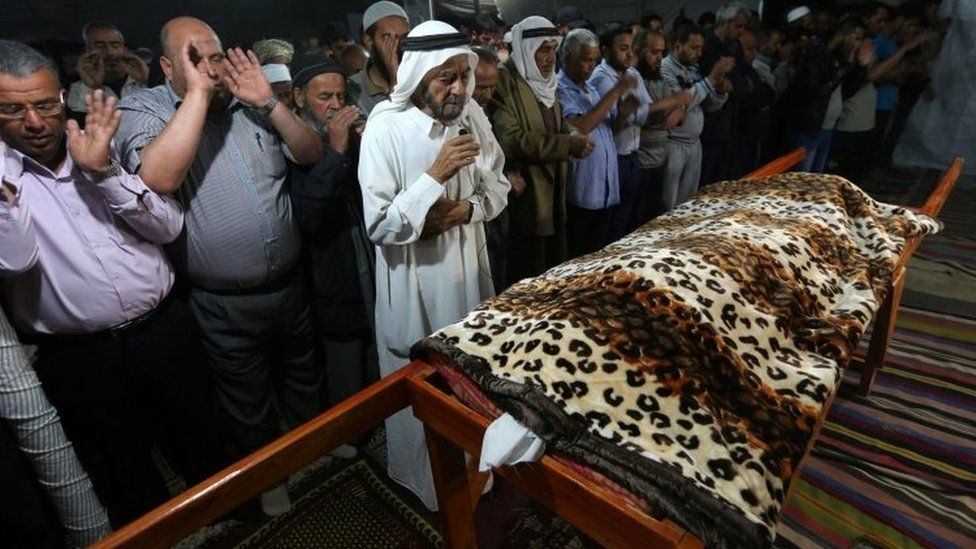 Mourners in Gaza pray during the funeral of the Palestinian woman who - according to medics - was killed by Israeli tank fire