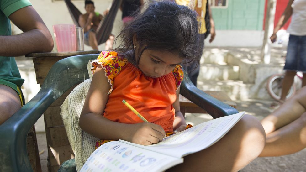 Seven-year-old Shayla Monterlaza, the granddaughter of a displaced woman, studies in front of the community's school with her family