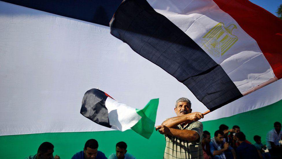 A Palestinian man waves the Egyptian and Palestinian flags as people gather in Gaza City to celebrate the signing of a reconciliation deal (12 October 2017)