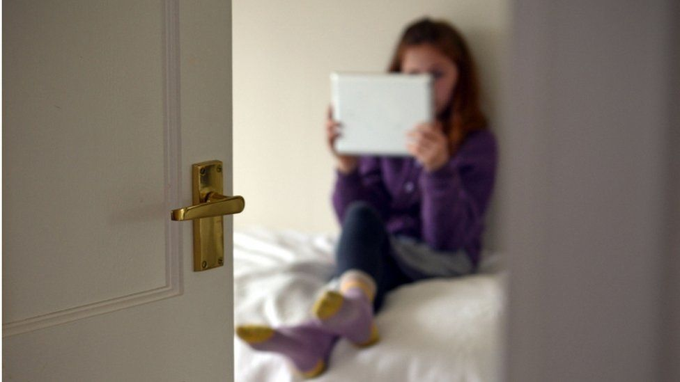 Girl sitting on bed, using a tablet