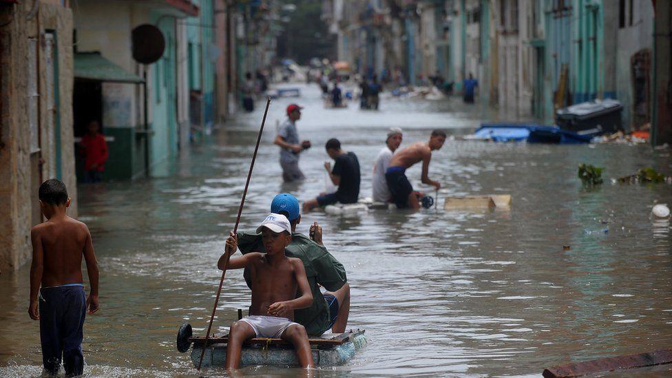 Cubans wade through a flooded street in Havana, on September 10, 2017.