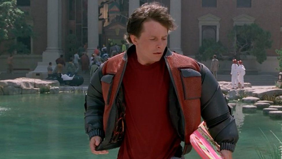 Marty McFly portrayed by Michael J. Fox in Back to the Future II holds his hoverboard outside the Town Hall