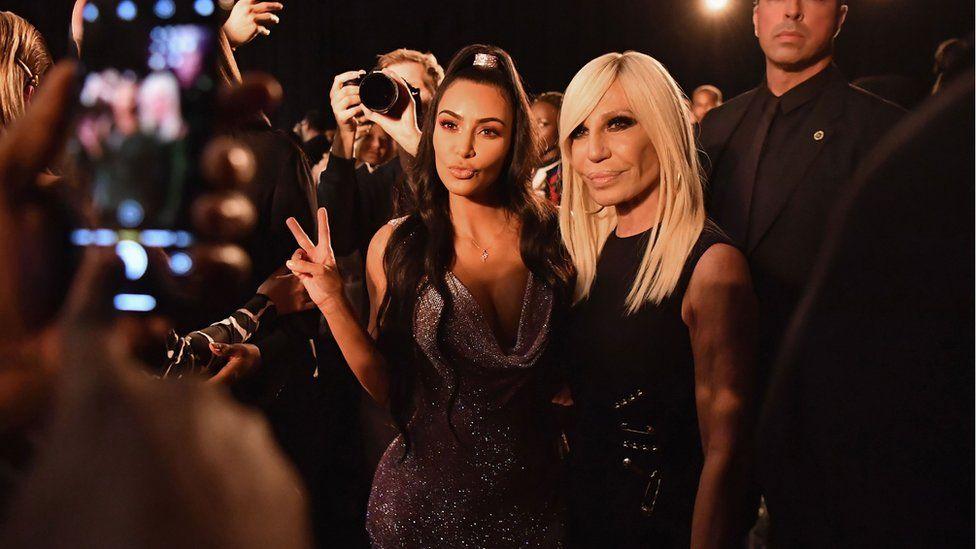 Kim Kardashian poses with Donatella Versace on a red carpet