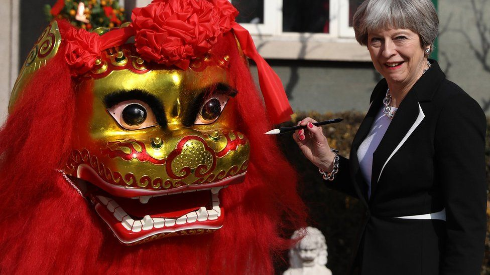 """Theresa May """"dots the eyes"""" of a dragon outside the British Embassy on 1 February 2018 in Beijing"""