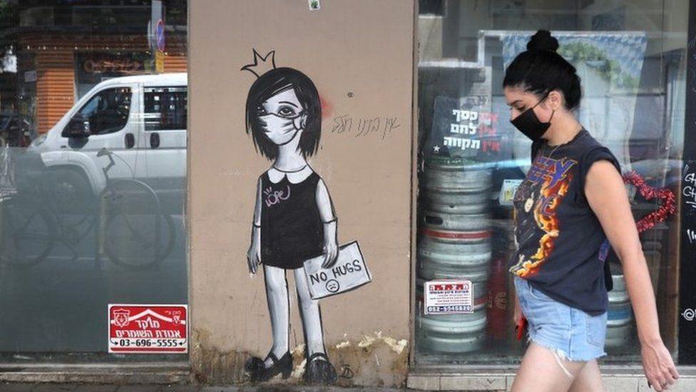 A woman walks by coronavirus graffiti in Tel Aviv (8 September 2020)