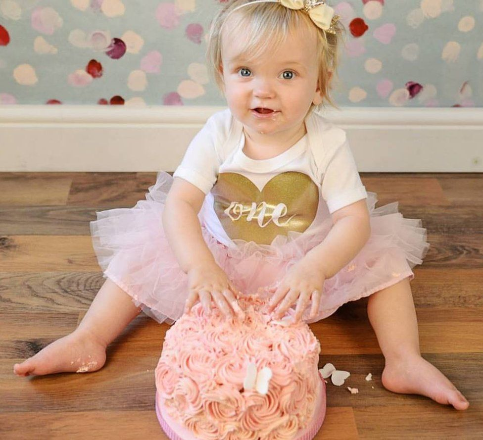 One-year-old Autumn Eden, wearing a pink tutu, sticks her fingers into a pink cake