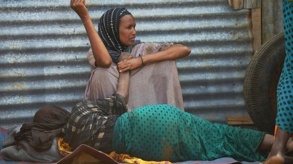 An elderly woman weakened by hunger lies on the ground as her daughter watches over her at a camp for the internally displaced on the outskirts of Baidoa town, the capital of Bay region of south-western Somalia