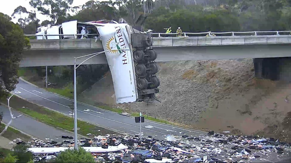 A truck hangs off an overpass bridge with its contents spilled across the motorway below