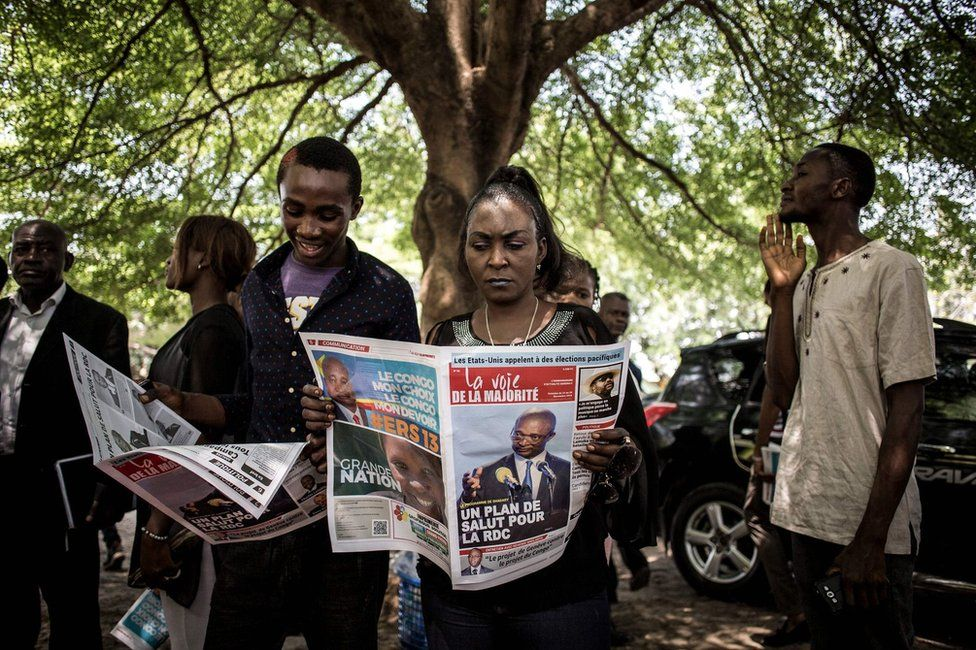 Supporters of the official DRCongo Presidential candidate, Emmanuel Ramazani Shadary, read a newspaper outside the Cathedral Notre-Dame Du Congo in Kinshasa on November 24, 2018, during the launch of his official electoral campaign.