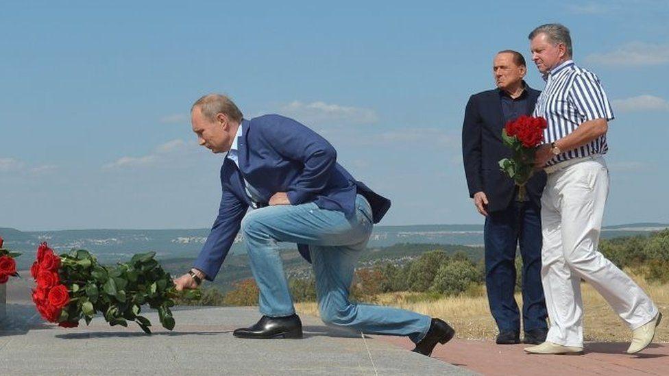 Russian President Vladimir Putin (left) and former Italian Prime Minister Silvio Berlusconi (second on the left) visit an Italian war cemetery near the Black Sea port of Sevastopol