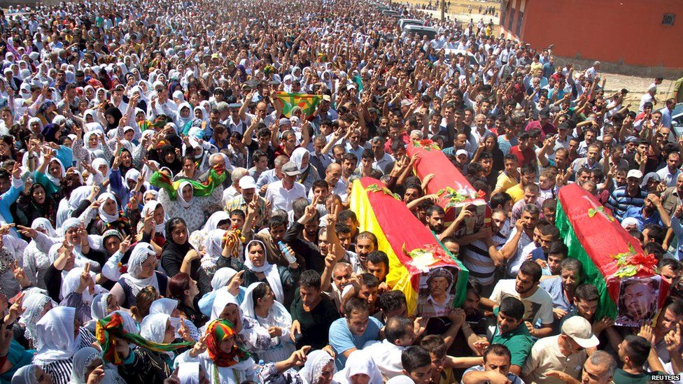 Mourners carry coffins of three Turkish Kurdish men killed during a funeral ceremony in the southeastern town of Silopi in Sirnak province on 8 August