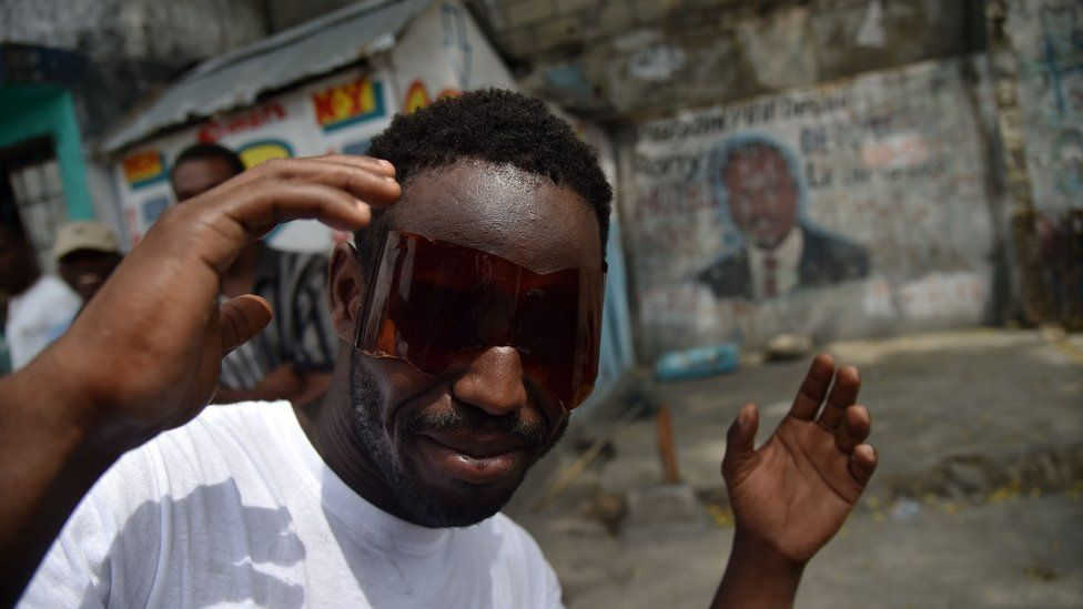 A man uses glasses he made from a plastic bottle to look the solar eclipse that was partially visible in Port-au-Prince, on August 21, 2017. The solar eclipse in Haiti was only partially visible, around a 73% in the north of the country, and around a 70% in the capital.