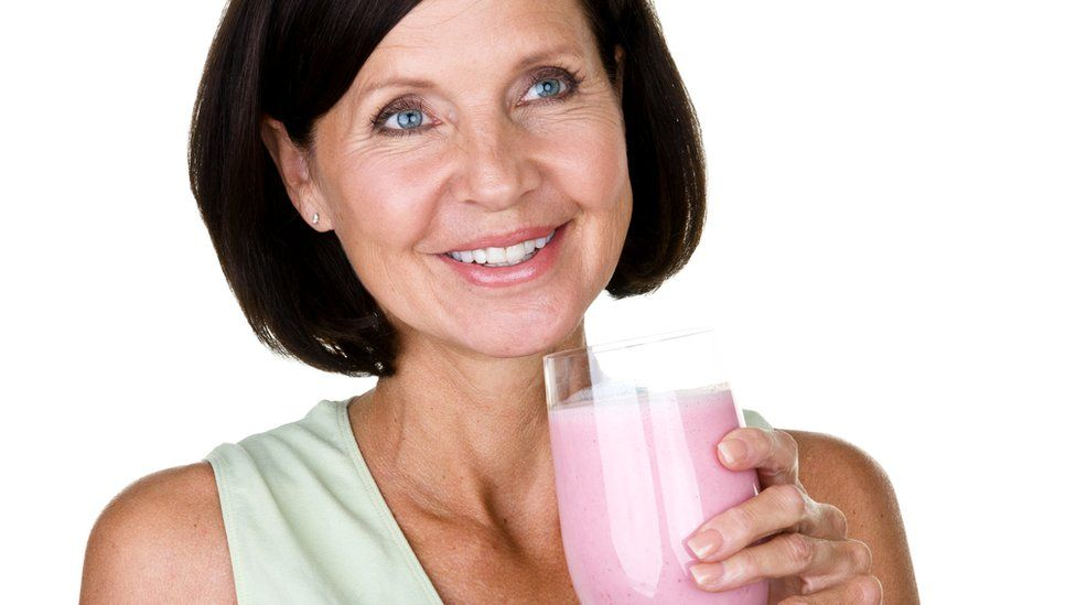 Older woman holding a glass of strawberry-flavoured drink