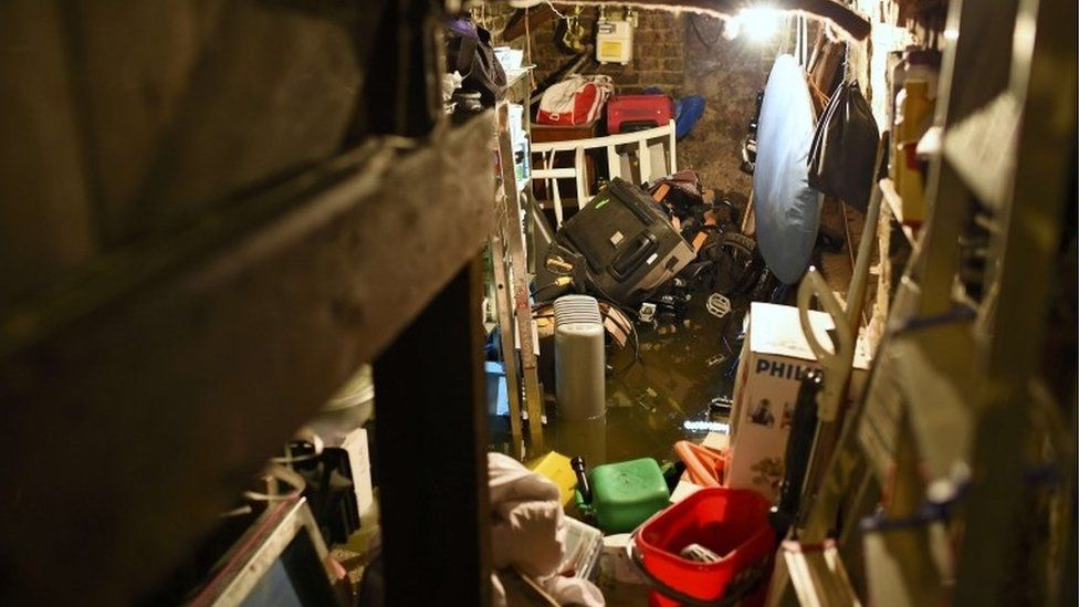 Floodwater engulfs objects in the cellar of house, after heavy rain in south London