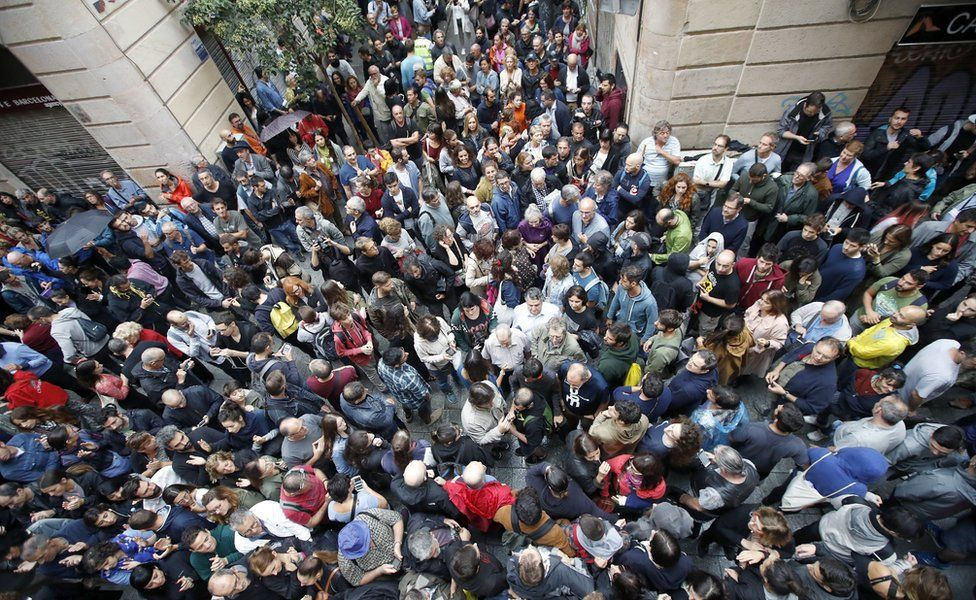 Hundreds of people wait outside a polling station set at Cervantes School in Barcelona, Catalonia, northeastern Spain, 01 October 2017