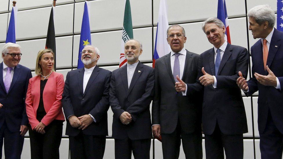 World diplomats stand and smile after signing the Iran nuclear deal in 2015