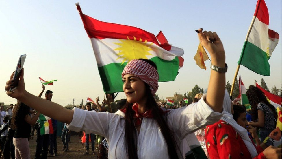 A woman poses for a selfie at a gathering in support of Kurdish independence in September