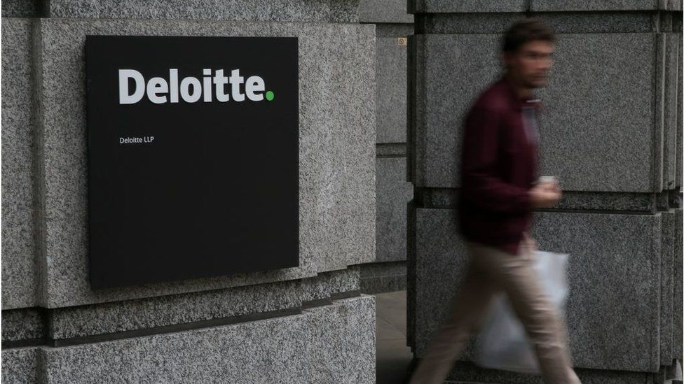 A man leaving Deloitte's offices