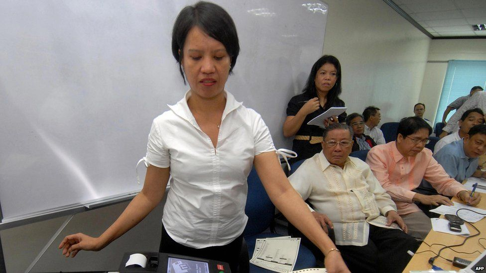 An employee (L) of Smartmatic demonstrates the function of election automation machine next to Philippine Commission on Elections (Comelec) officials