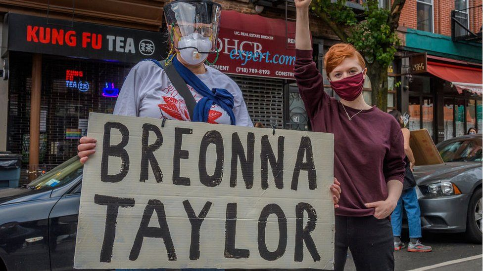 Protestors holding up sign with Breonna Taylor's name