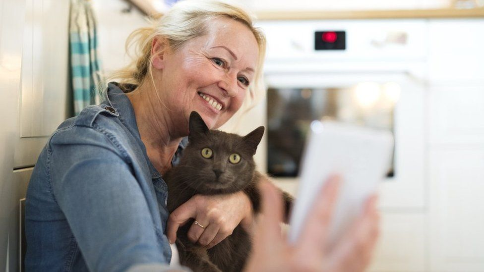 Woman taking selfie with cat