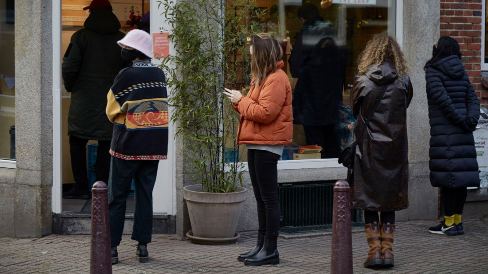 People line up outside a take away restaurant in Amsterdam, Netherlands