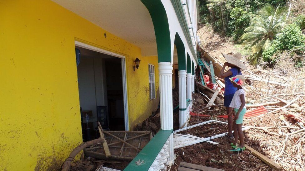 Debra Charles-Marks and her daughter Jeanette look at the damage at the family's resort in Delices