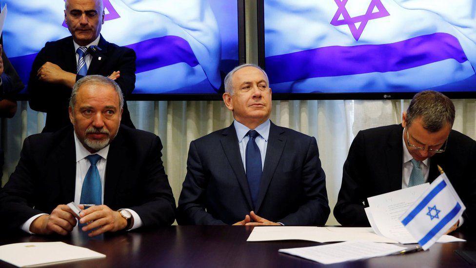 Avigdor Lieberman (L) and Benjamin Netanyahu (C) sign a coalition agreement in Jerusalem (25 May 2016)