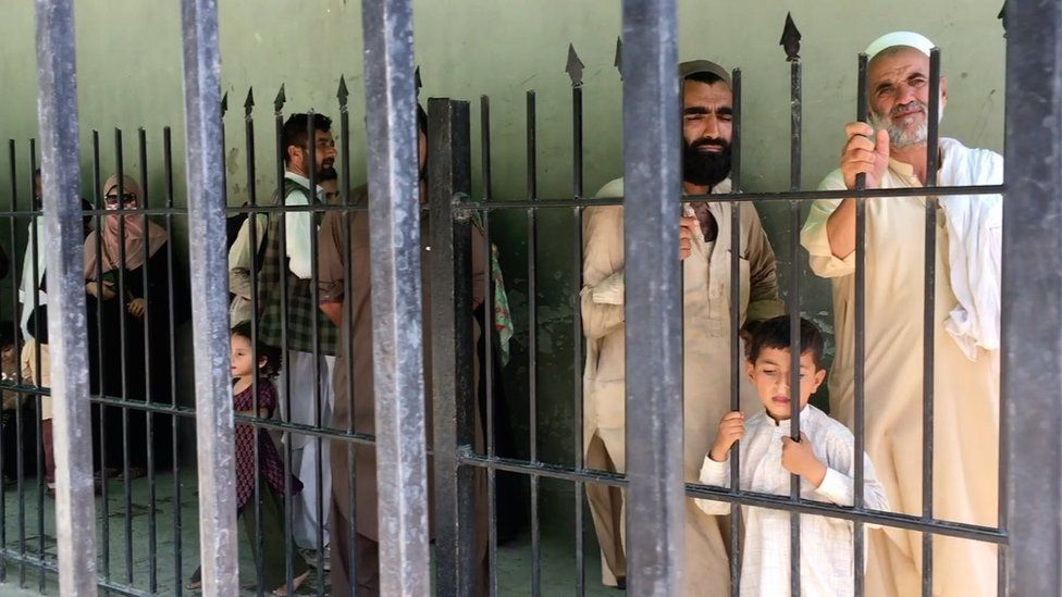 Afghans wait behind a fence to cross into Pakistan at Torkham