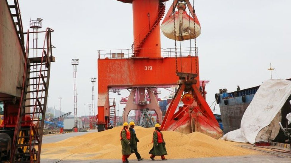 """Workers walk past imported soybeans at a port in Nantong in China""""s eastern Jiangsu province on April 4, 2018"""