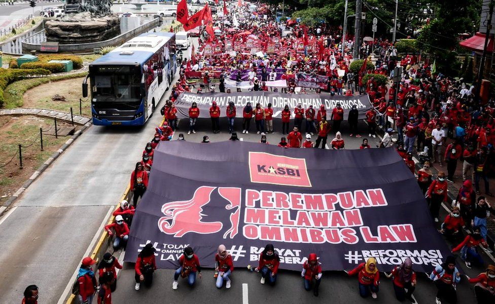 Women carry posters at a march for International Women's Day in Jakarta, 8 March 2020
