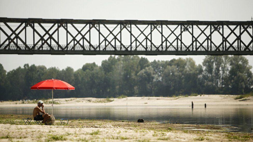 A young man sits under an umbrella at the Po River near the Ponte della Becca bridge in Linarolo, near Pavia, northern Italy