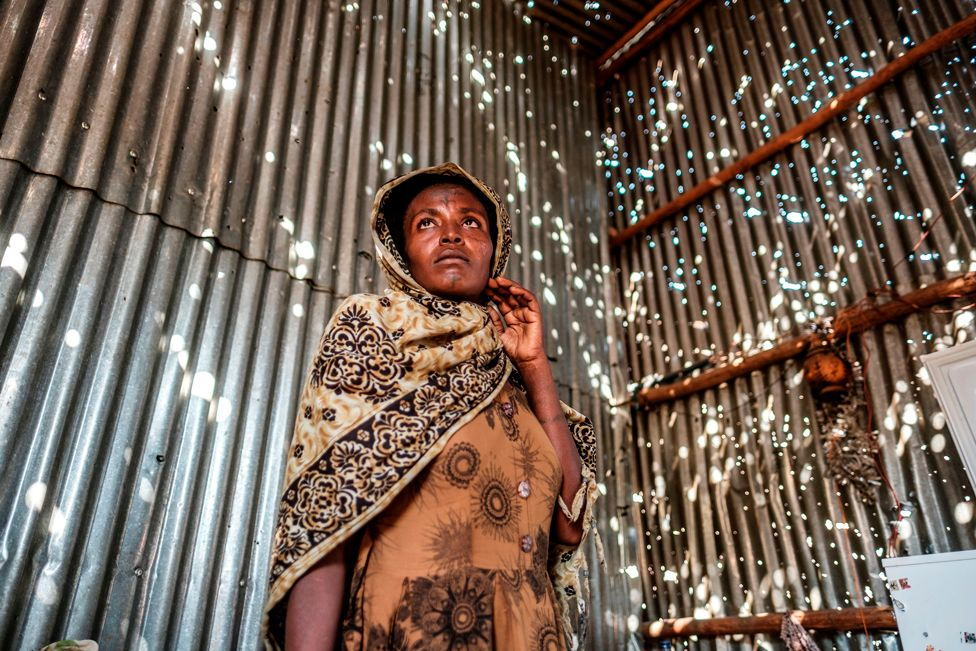 A woman stands in a metal sheet room that was damaged by shelling, in Humera, Ethiopia