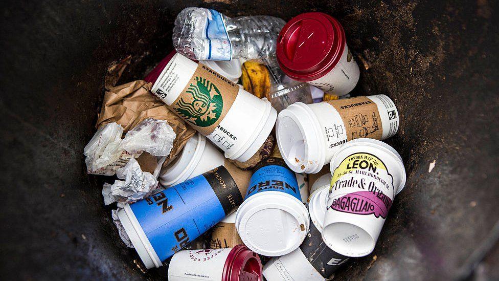 Single-use coffee cups in a bin